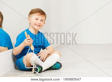 Portrait of schoolboy wearing sportswear, holding jumping rope and sitting on the floor of light gym