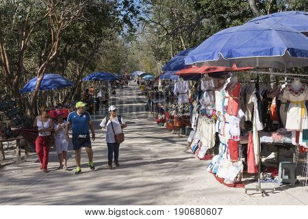CHICHEN ITZA YUCATAN MEXICO - FEBRUARY 24 2017: The popular Maya ruins of Chichen Itza is a tourist trap full of vendors selling textile products sculptures and other souvenirs to visitors.