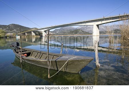 Traditional little green boat in Neretva river near Rogotin bridge