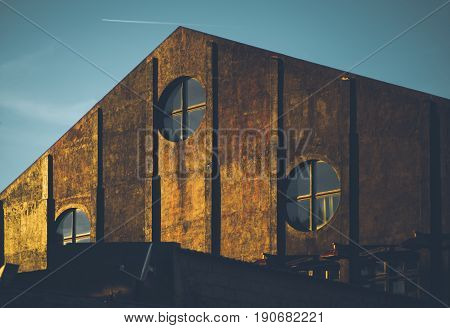 Old pyramidal industrial building with round windows lighted by golden sunset triangle form port warehouse in Lisbon with three bull's-eyes windows illuminated by yellow morning sun with teal sky