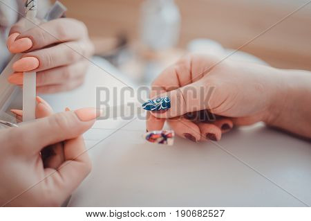Female Client During Gel Manicure With Manicurist Displaying Samples Of Patterns On Nails