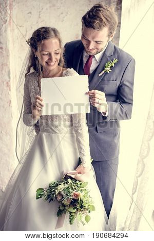 Bride and groom holding blank placard