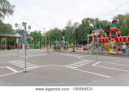 Nizhny Novgorod, Russia. - August 03.2016. Children playground game complex in Park Switzerland. The girl learns to cross the road correctly at a toy crossroads with markings and sphetofores.