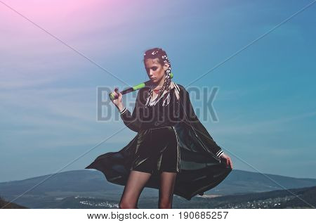 girl. Pretty woman or cute girl with stylish long braids brunette hair makeup in fashionable black sportswear posing with baseball bat in hand on mountain landscape. Sport fashion and training