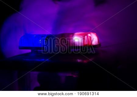 Red Light Flasher Atop Of A Police Car. City Lights On The Background. Police Government Concept