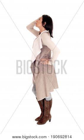 A young Hispanic woman standing in profile in a deerskin coat and brown boots isolated for white background.