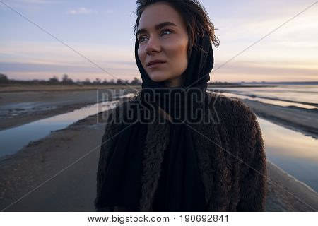Beautiful girl in a coat walks on the lake in winter and see to the sundown,