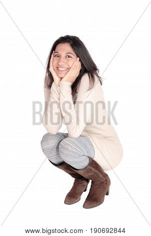 A beautiful young Hispanic woman in a knitted dress and brown boots crouching on floor the face in her hands isolated on white background.