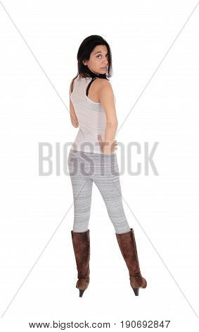 A lovely Hispanic woman standing from the back in gray leggings and brown boots isolated for white background.