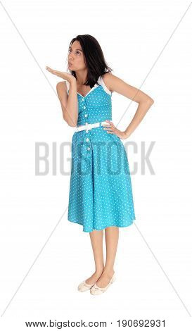A beautiful young woman in a blue dress standing isolated for white background and blowing a kiss.