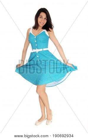A smiling gorgeous young woman standing in full length in a blue dress and holding the dress up isolated for white background.
