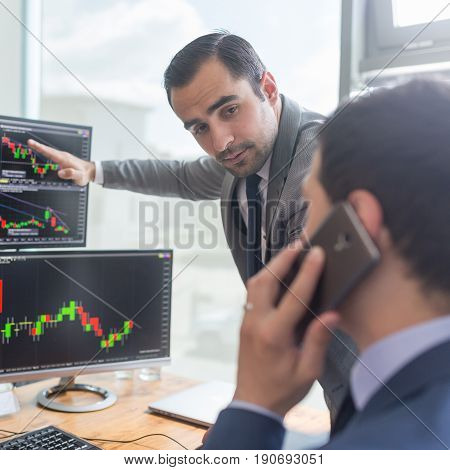 Businessmen trading stocks online. Stock brokers looking at graphs, indexes and numbers on multiple computer screens. Colleagues in discussion in traders office. Business success concept.