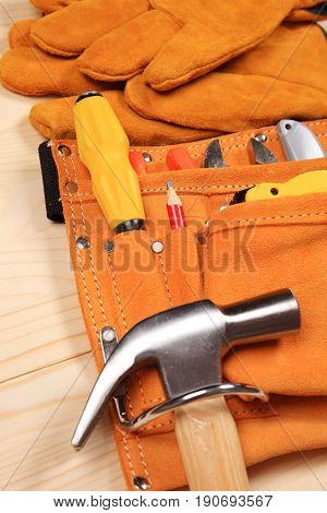 Hammer, pliers, red pencil, work gloves and other tools isolated on a wooden background