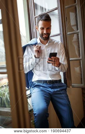 Male businessperson near window in office calling business partner on cell phone