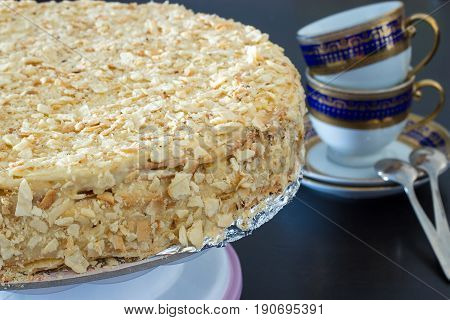 Round multi-layered cake Napoleon with custard on a black wooden table background. Selective focus