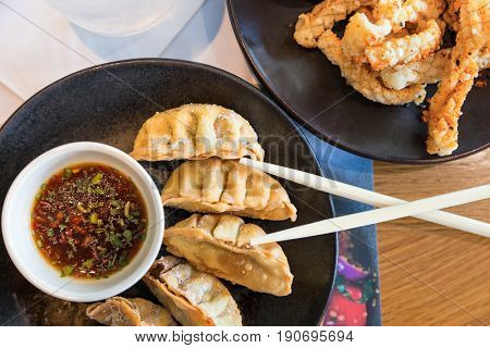 Japanese snacks of fried gyoza and strips of seasoned, crispy squid. Served with a soy, herb and chilli dipping sauce and presented on black plates with wooden chopsticks.