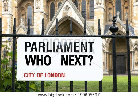Sign in the style of a London Street sign asking Parliament, who next? Black white and red banner against wrought iron railings, with Westminster Abbey in the background.