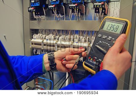 engineer adjusts electrical circuit of the automation and makes a multimeter a measurement. Hands of an electrician close-up with a multimeter on background of an electrical terminal block with wires