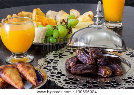 Dried date palm fruits fresh orange juice samosa snack and blurred fruit background concept iftar in the holy month Ramadan.