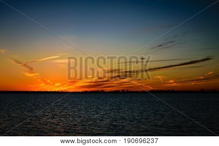 Wispy clouds and sunset by the lake