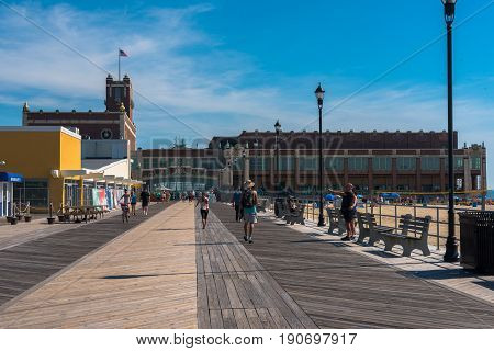 Asbury Park NJ USA -- June 11 2017 People walking and bicycling on the boardwalk by Convention Hall in Asbury Park on a summer morning. Editorial Use Only.