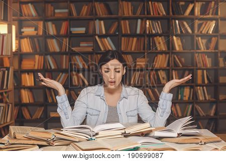 Young female study in the library incomprehension