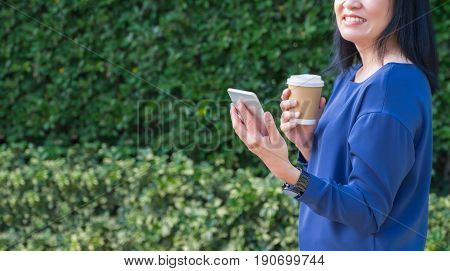 Woman in causal cloth holding to go coffee cup and smile while use mobile phone outside house at green hedgeLeave copy space for adding your text.