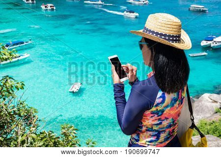 Traveller woman with colorful swimming suit use mobile take photo of view at top of mountain and speed boat in seaSummer vacation traveling.