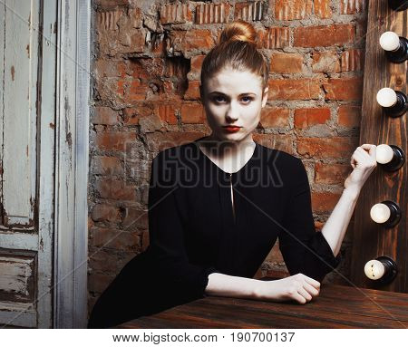 young stylish woman in make up room with mirror, diva actress before perfomance thinking art. loft interior close up