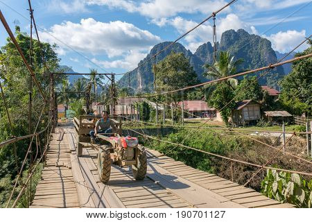 Vang Vieng, Laos - January 19, 2017: Wooden bridge across Nam Song River in Vang Vieng village, Laos.