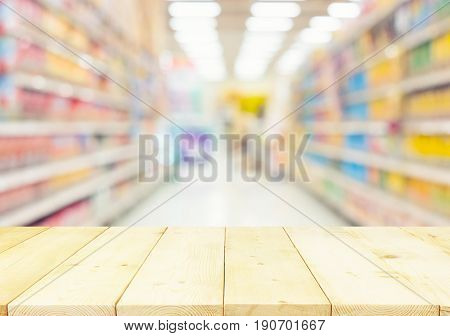 Blurred photo of aisle and shelf in supermarket montage with wood table for background.