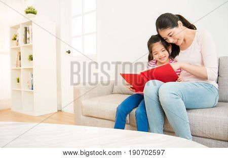 happy asian chinese mother and little daughter girl reading a book in the morning together in the living room at home. family activity concept.