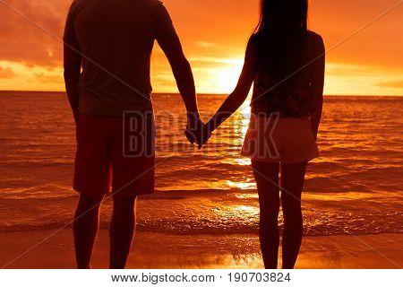 Couple silhouette holding hands watching sunset on beach, Hawaii honeymoon vacation travel getaway.