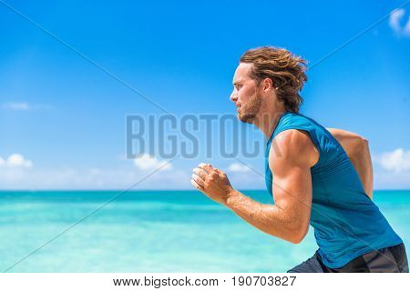 Healthy sport runner man running sprint on beach ocean background. Sports athlete active lifestyle in summer outdoor tropical landscape.