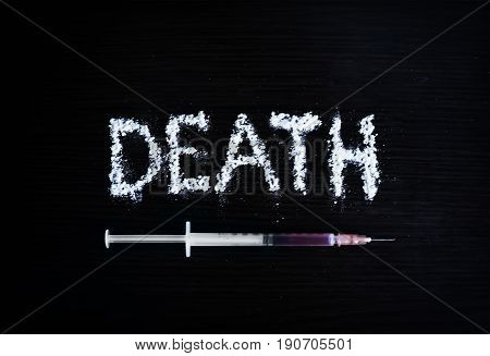 inscription death cocaine accented by a syringe of heroin on a black background