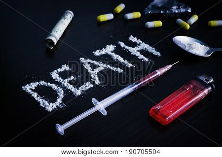 Drugs on the table next to death closeup view from above. The concept of drug addiction.