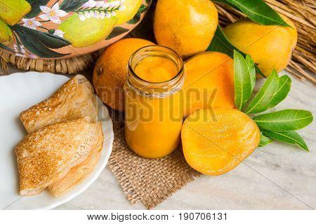 Homemade Mango Jam with fresh fruits, slices, pancakes on a white marble. Caramelized Mango Jam marmalade in glass jar on burlap. Home cooking mango chutney. Selective focus.