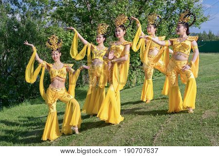 group of five asian women actresses in traditional chinese yellow costumes outdoor