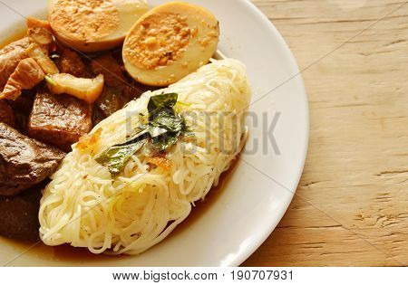 thin rice noodle with pork entrails and tofu topping egg on plate