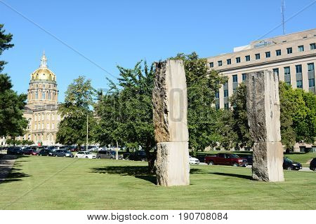 DES MOINES, IOWA - AUGUST 20, 2015: Five Stones One tree public art installation. By Luther Utterback, The two Limestone pillars and Ginko Tree are organized as points of an isosceles triangle.