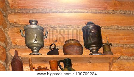 Samovar objects of Russian antiquity, against the background of the old rural wooden wall