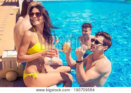 Party at smimming pool. Group of cheerful couples drinking cocktailsin the pool. They look happy
