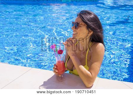 portrait of young sexy girl at swimming pool, wearing bikini. She is wearing sunglasses and looking for somebody. drinking red cocktail during vacation. Pool party