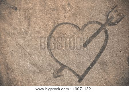 Heart on dusty and dirty wooden floor.
