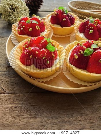 Homemade strawberry tart in paper cup on wood plate. Fruit tart or strawberry tart sprinkle with chopped pistachio and decorated with mint leaf. Delicious strawberry tart on rustic wood background. Homemade fruit tart or strawberry tart.