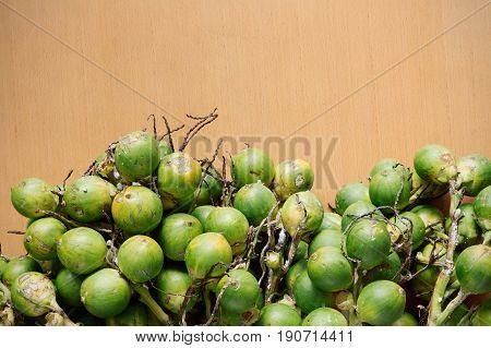 Green betel nut on a wooden floor.