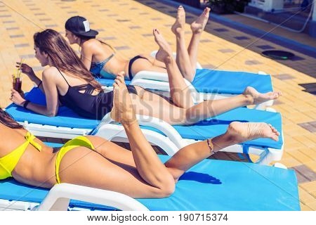 Sexy fit girls in swimwearare drinking cocktails while sunbathing on the chaise longue near the pool. Fit shapes