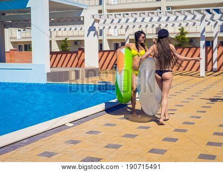 Two beautiful sexy hipster girls going with swimming circles or inflatable ring near swimming pool. They are and laughing. graceful beautiful figure and shape