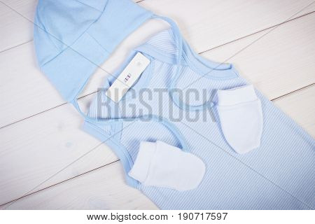 Pregnancy Test With Positive Result And Clothing For Newborn, Concept Of Expecting For Baby