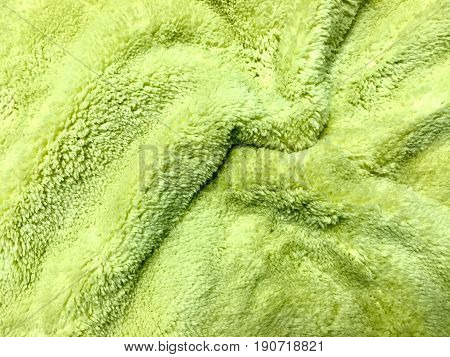 Fabric Texture Close Up of Light Green Rippled Plush Pattern Background with Copy Space for Text Decoration.